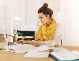 Woman Reviewing Papers and using a Computer