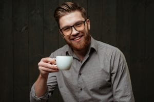 Man Looking Content Holding a Cup of Coffee